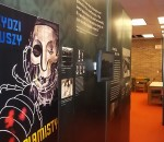 The traveling holocaust exhibit in Nash Library is a walk-through display that features mixed media like this wall with pictured artifacts and video clips.