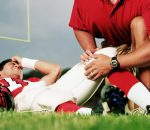 Football team doctor with injured player on field