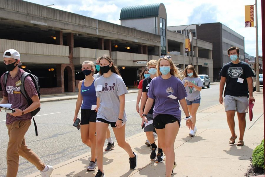A group of students walking along West Eighth Street are seen practicing safe social distancing and wearing masks in accordance with guidelines established.
