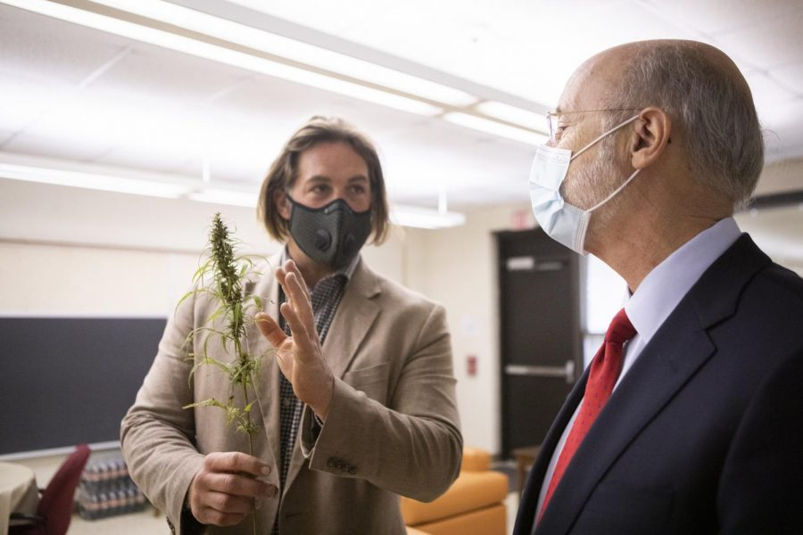 Pennsylvania Gov. Tom Wolf, right, stands with Eric Titus White, a hemp farmer who is showing Wolf a cutting of industrial hemp as part of Wolf's visit to Monroe County on Oct. 13. There, Wolf discussed the benefits of legalizing recreational marijuana, including economic growth and restorative justice benefits for incarcerated Pennsylvanians.