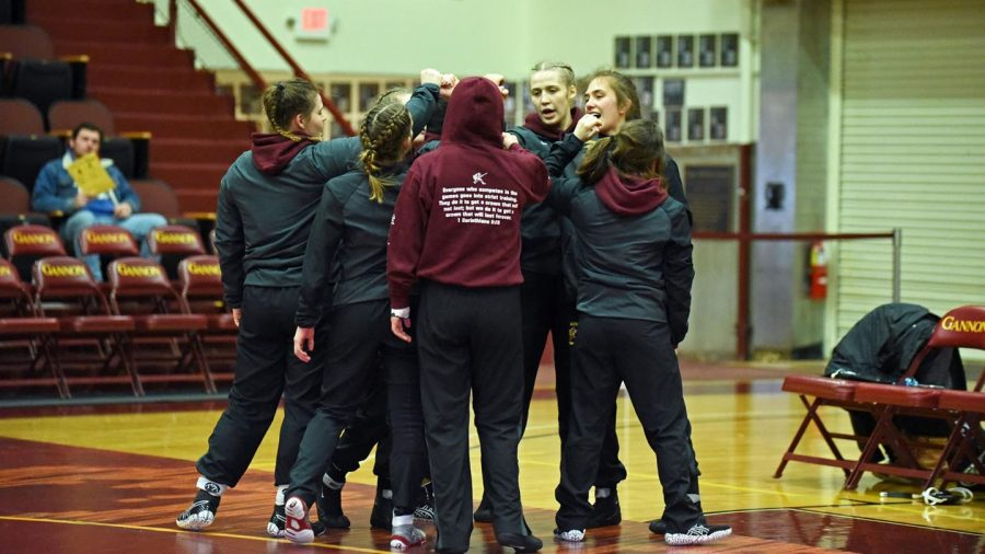 The Gannon women's wrestling team huddles prior to competing during the 2019-20 season.