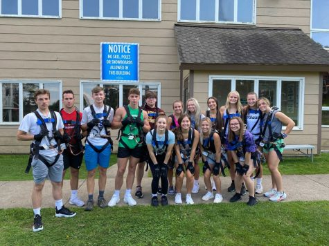 Freshmen students in the outdoor adventure FYT group get suited up for the ropes course at the Peek'n'Peak Resort during Welcome Week activities.